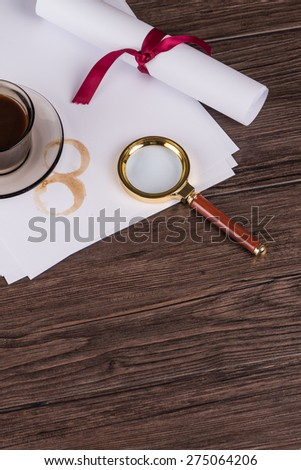 Coffee cup, paper sheets and detective magnifying glass on old Wooden table. - stock photo