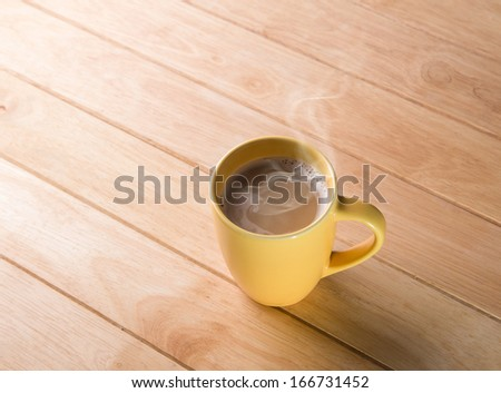 Coffee cup placed on a wooden floor.