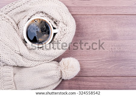 Coffee cup, scarf and hat hand made on a wooden background. Top view. Concept cozy atmosphere with a cup of coffee in winter - stock photo