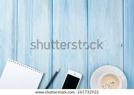 Coffee cup, smartphone and blank notepad on wooden table background. Top view with copy space - stock photo