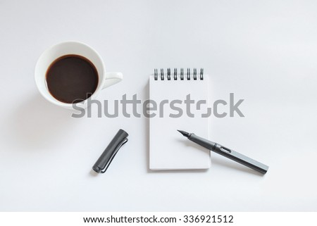 Coffee cup, spiral notebook and pen on white background - taken in natural light  with strong shodow to create realistic indoor mood