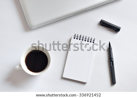 Coffee cup, spiral notebook, laptop, and pen on white background - taken in natural light  with strong shodow to create realistic indoor mood