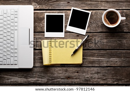 Coffee cup, white laptop keyboard, instant photos and notepad with pen on old wooden table. - stock photo