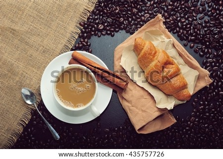 Coffee cup with a croissant and fresh coffee beans on dark background. - stock photo