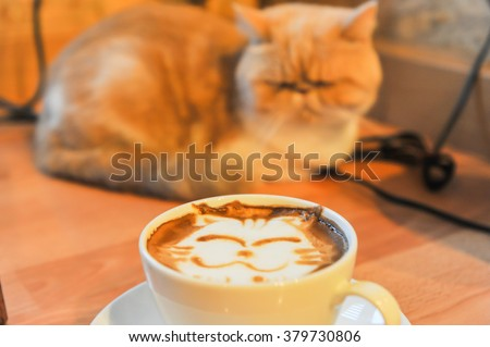 Coffee cup with artistic cream cat face decoration, blured cat backgroud - stock photo