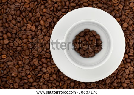 Coffee cup with beans. Above view. On beans background