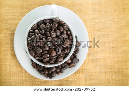 Coffee cup with beans on the wood board.