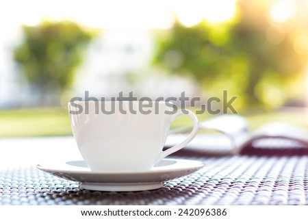 Coffee cup with book on blurred green nature background - chill out concept - stock photo