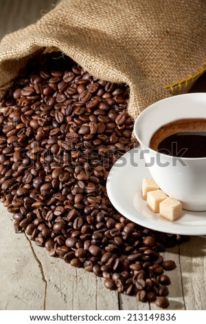 Coffee cup with burlap sack of roasted beans against dark wood background - stock photo