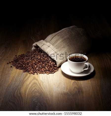 Coffee cup with burlap sack of roasted beans on rustic table - stock photo