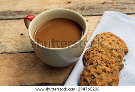 Coffee cup with chocolate cookie on dark wooden background