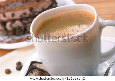 Coffee cup with chocolate dessert cake aside
