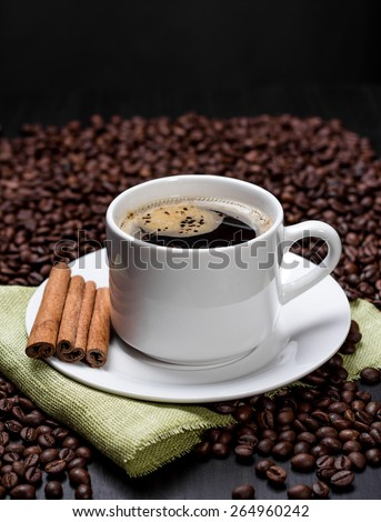Coffee cup with cinnamon on rustic table - stock photo