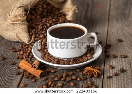 Coffee cup with cinnamon sticks and coffee bag on wooden table - stock photo