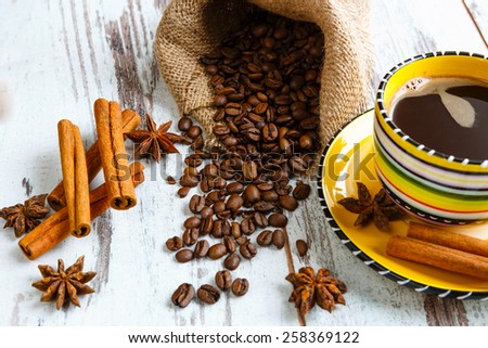 Coffee cup with coffee beans, cinnamon, star anise on old wooden background boards - stock photo