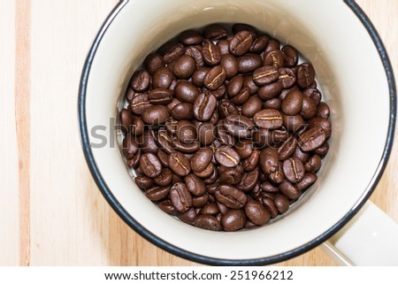 Coffee cup with coffee beans in the cup