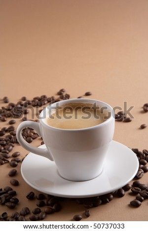 coffee cup with coffee beans on brown background - stock photo