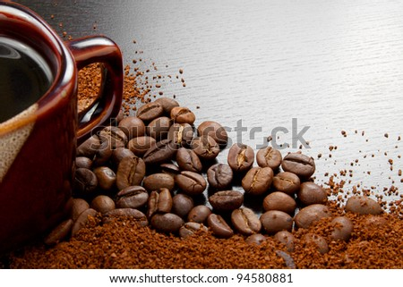 Coffee cup with coffee beans on dark table - stock photo