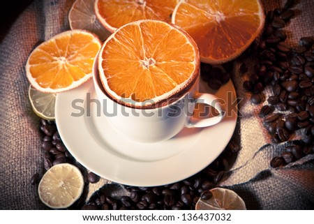 Coffee cup with coffee beans, orange and lemon on yuta material