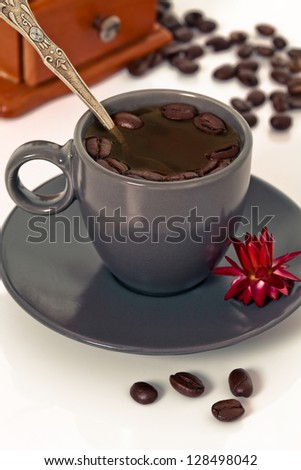 Coffee cup with coffee grinder and orchid flower - stock photo