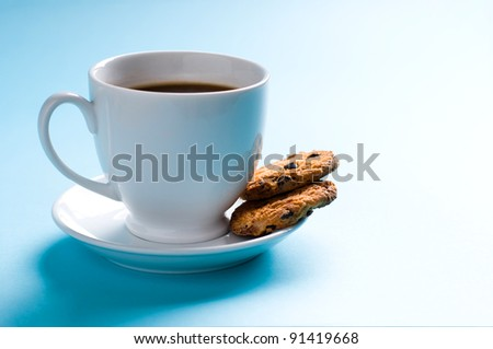 Coffee cup with cookies on blue background - stock photo
