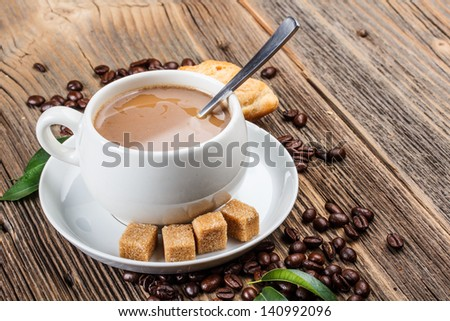 Coffee cup with fresh coffee beans and lump sugar - stock photo
