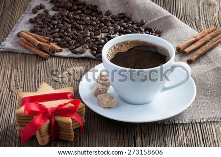 Coffee cup with gingerbread cookies, cinnamon and cane sugar on wooden background - stock photo