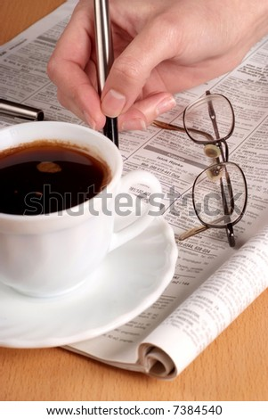 Coffee cup with glasses and newspaper. Focus on hand. - stock photo
