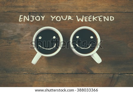 """coffee cup with happy faces next to """"enjoy your weekend"""" phrase background. vintage filtered. happy weekend concept - stock photo"""
