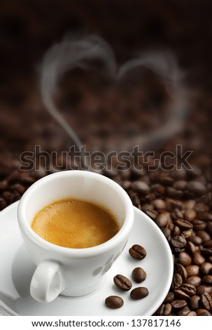 coffee cup with heart- shaped steam on background of coffee beans - stock photo