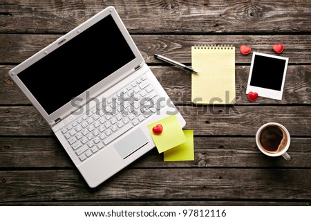 Coffee cup with laptop, instant photos and notepad on old wooden table. - stock photo