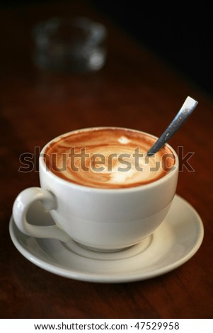 Coffee cup with milk on the table. Cup of cappuccino, cup of coffee, cup of coffee on brown wooden table vertical view. Cup of coffee on the table. Latte on a wood table. Hot Coffee in a cup on table. - stock photo
