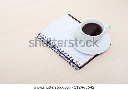 Coffee cup with note book on table - stock photo