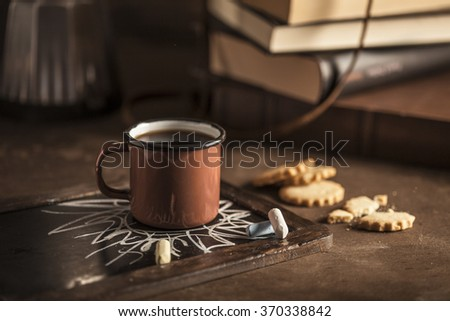 Coffee cup with old books and a retro camera in a wooden table