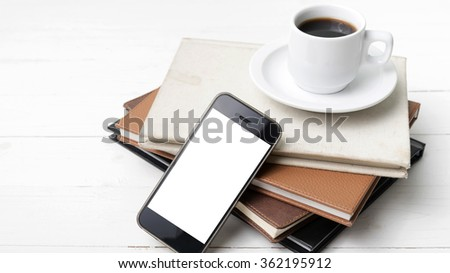 coffee cup with phone and stack of book on white wood table