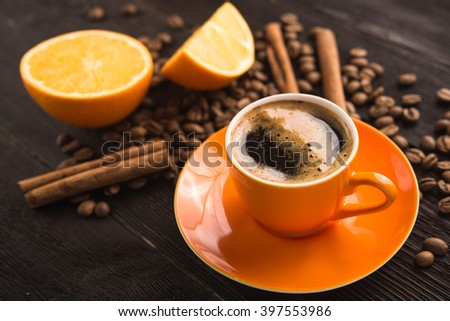 coffee cup with roasted beans and orange fruit
