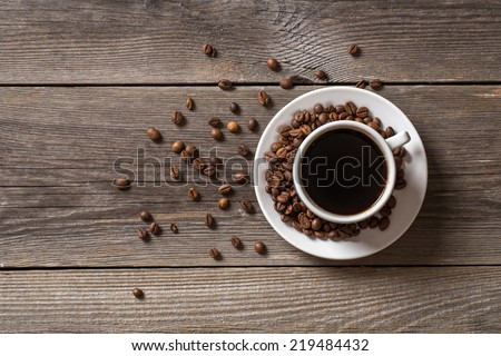 Coffee cup with roasted coffee beans on wooden table. View from top - stock photo