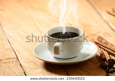 Coffee cup with smoke and coffee beans around  - stock photo