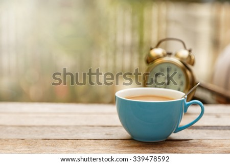 Coffee cup with spoon and alarm clock put on wooden floor with copy space - stock photo