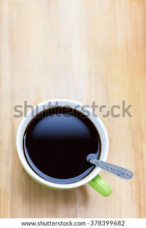 Coffee cup with spoon put on wooden floor with copy space, abstract and vintage style, top view