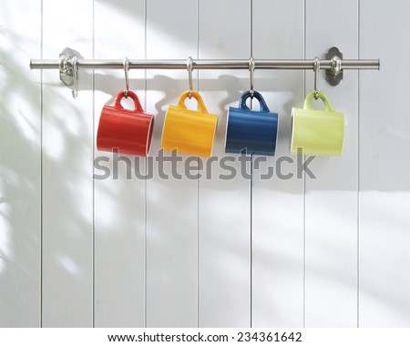 coffee cups hanging on hooks of kitchen wall.