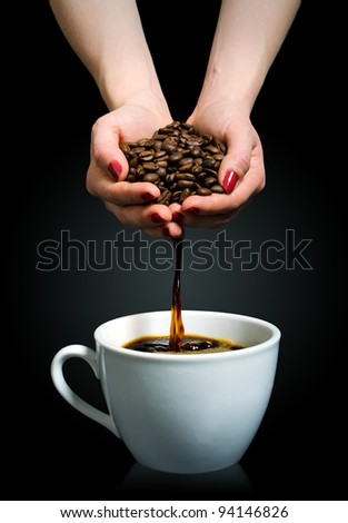 Coffee flows from a handful of beans into a cup - stock photo