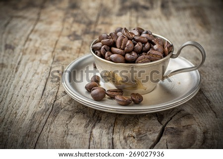 coffee grains in cup on grunge wooden background - stock photo