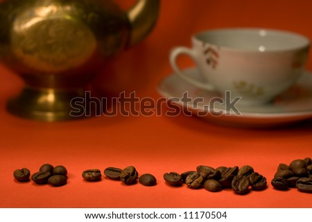 Coffee grains on red background with cup and pot