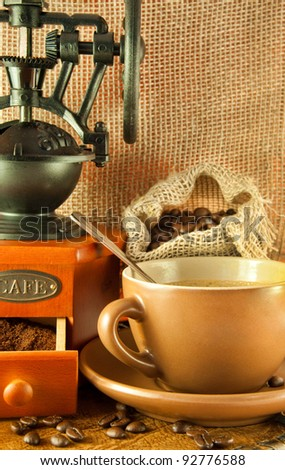 Coffee grinder in a retro style, a cup of coffee on grange background