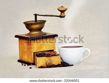 coffee grinder with coffee beans an cup of hot black coffee