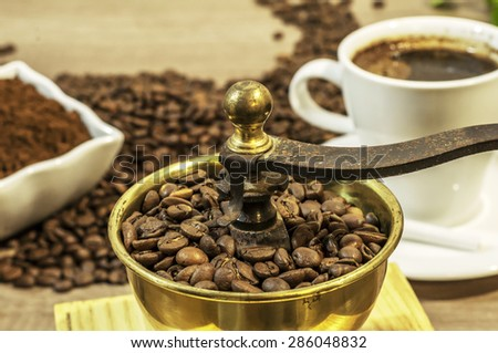 Coffee grinder with coffee beans and ground coffee in bowl on wooden table - stock photo