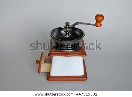 Coffee grinder with hand millstone. Side view with opened box - stock photo