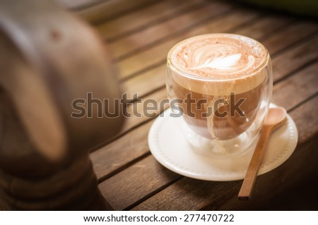 Coffee in a cup on wooden background - stock photo