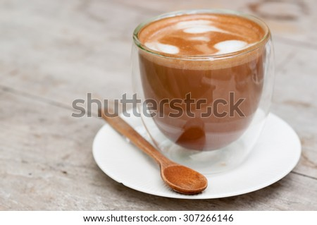 Coffee in a cup on wooden table - stock photo